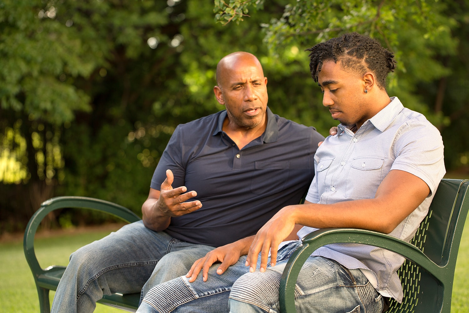 mentor speaking to a young man on a park bench